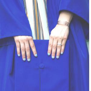 closeup of college graduate in robe holding cap