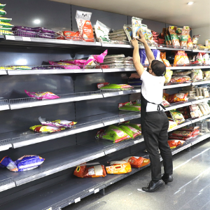 grocery worker reaching to an empty top shelf