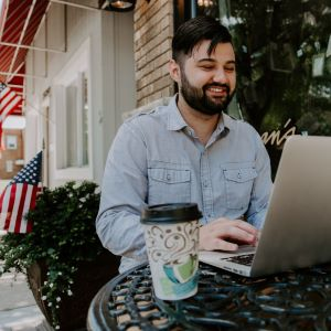 man on laptop with coffee sitting outside